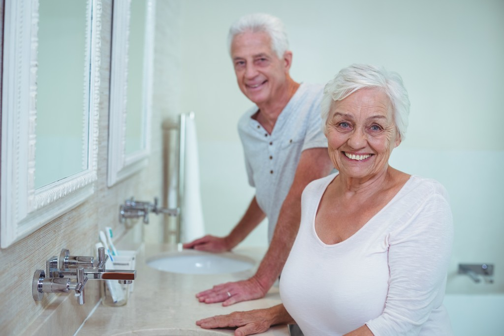 Portrait of senior couple standing by mirror in bathroom