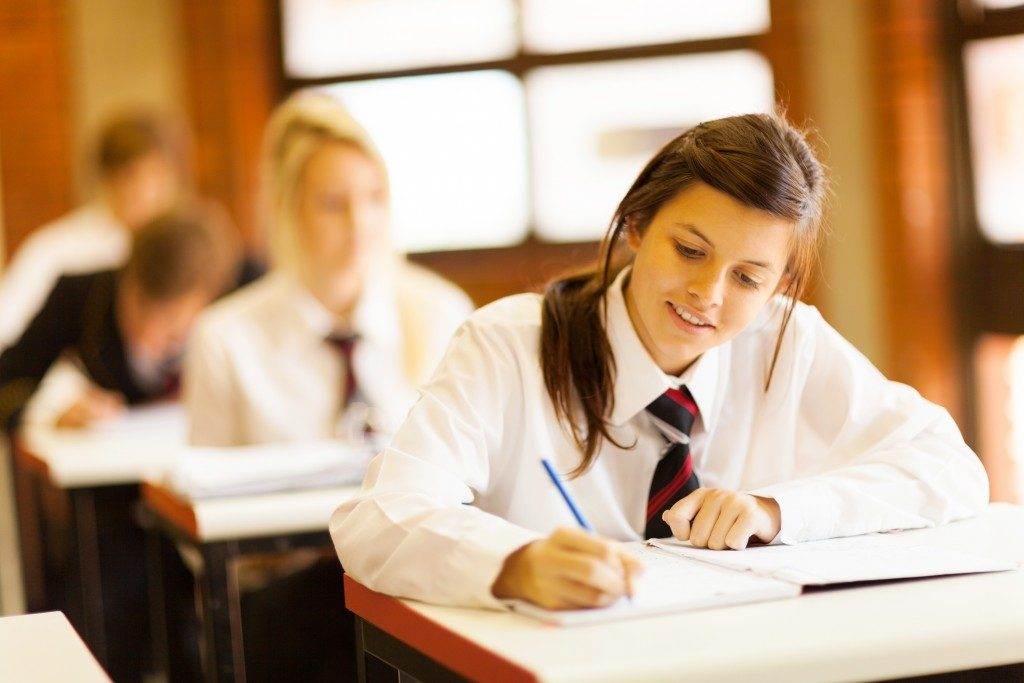 students writing on their desk inthe classroom