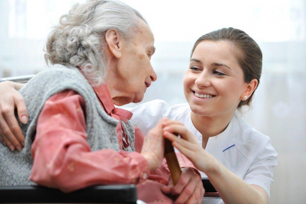 senior in wheelchair talking to a nurse