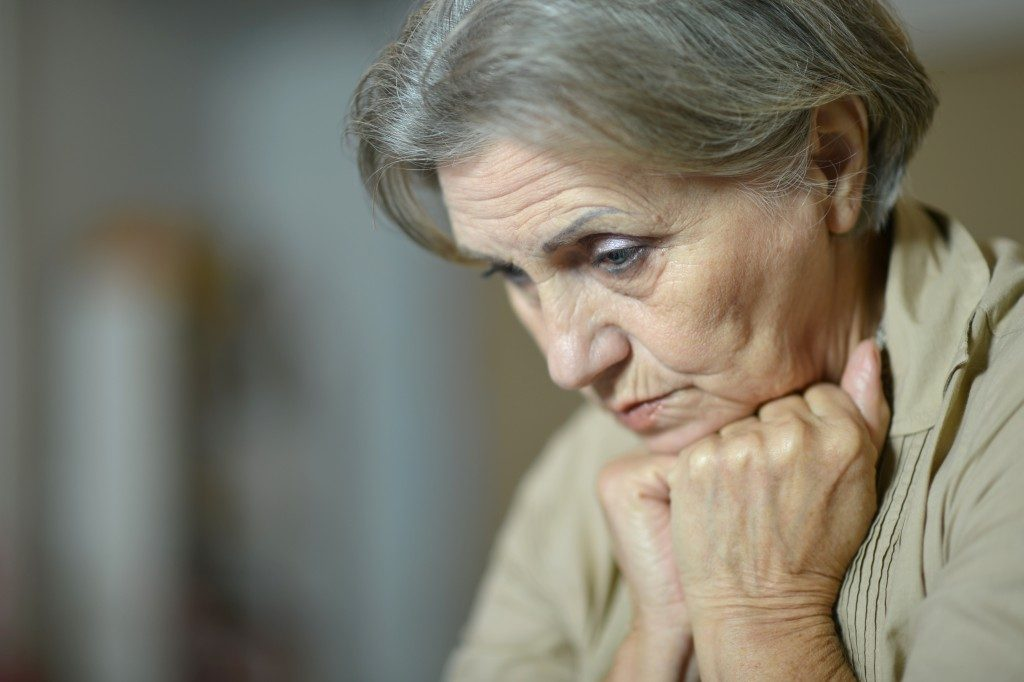 upset elder with her chin above her closed hands