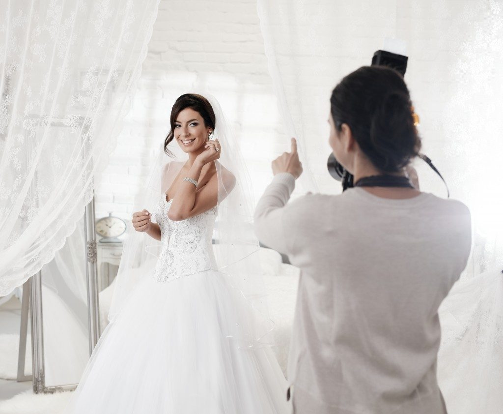 Female photographer taking pictures of bride