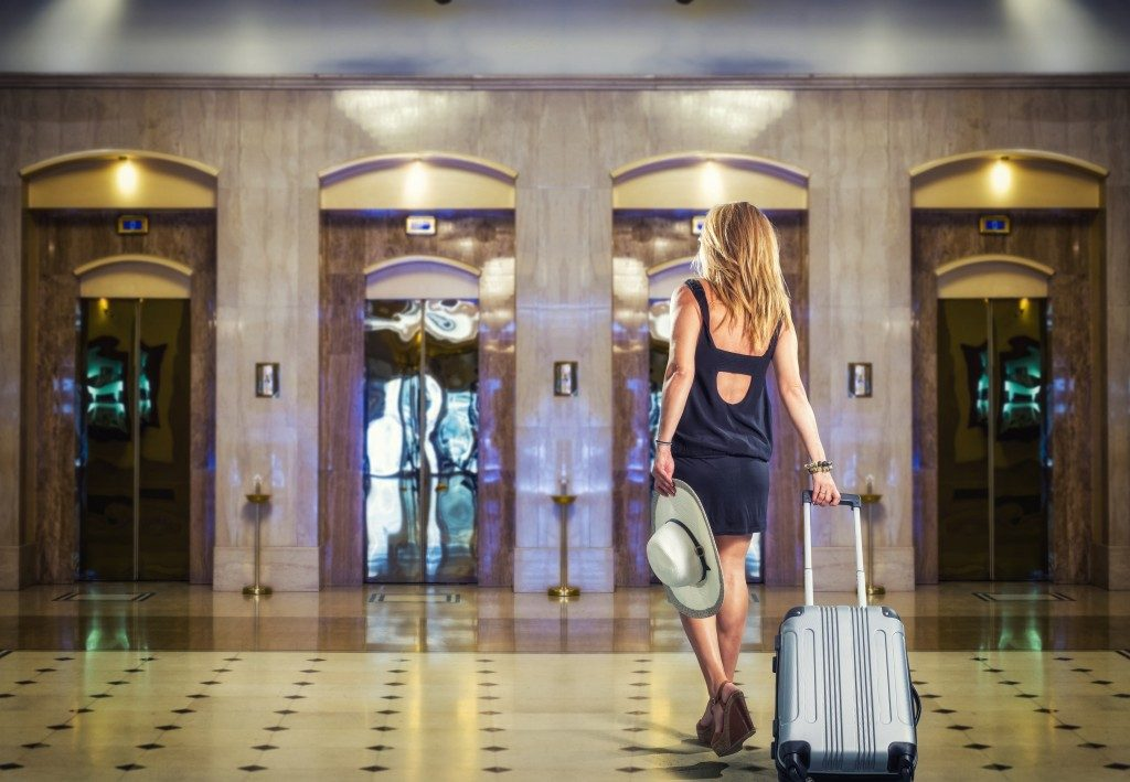 Woman with suitcase entering hotel