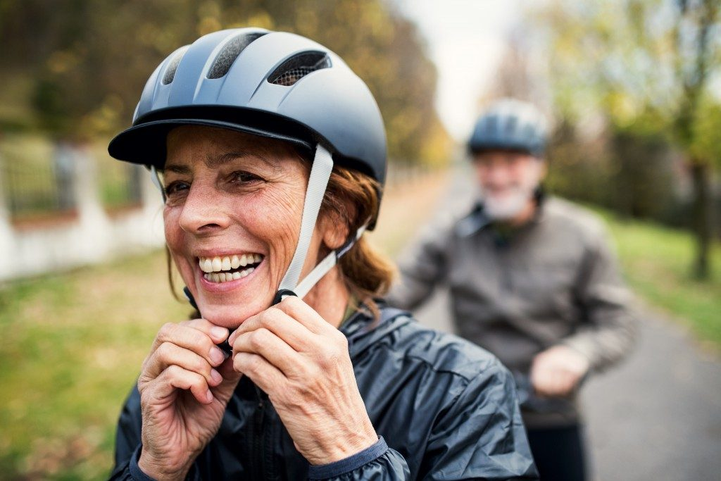woman putting on a helmet for biking