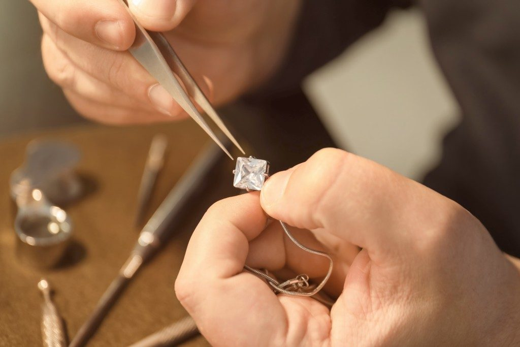 person fixing a jewelry