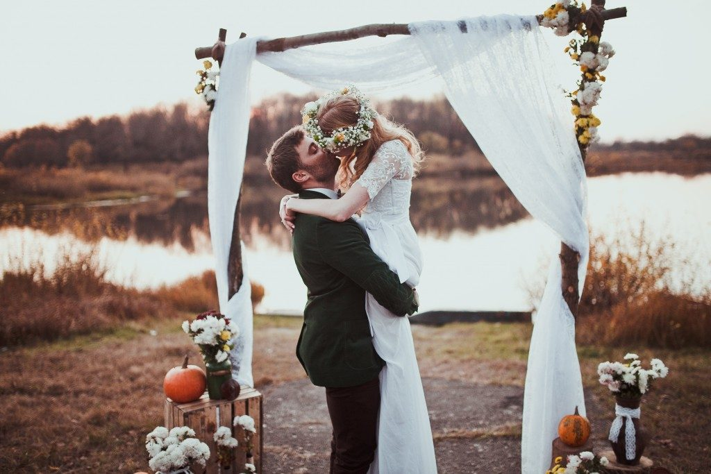 groom and bride kissing under a small wedding marquee