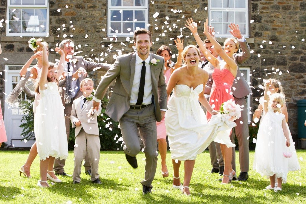 guests throwing confetti at newlywed couple