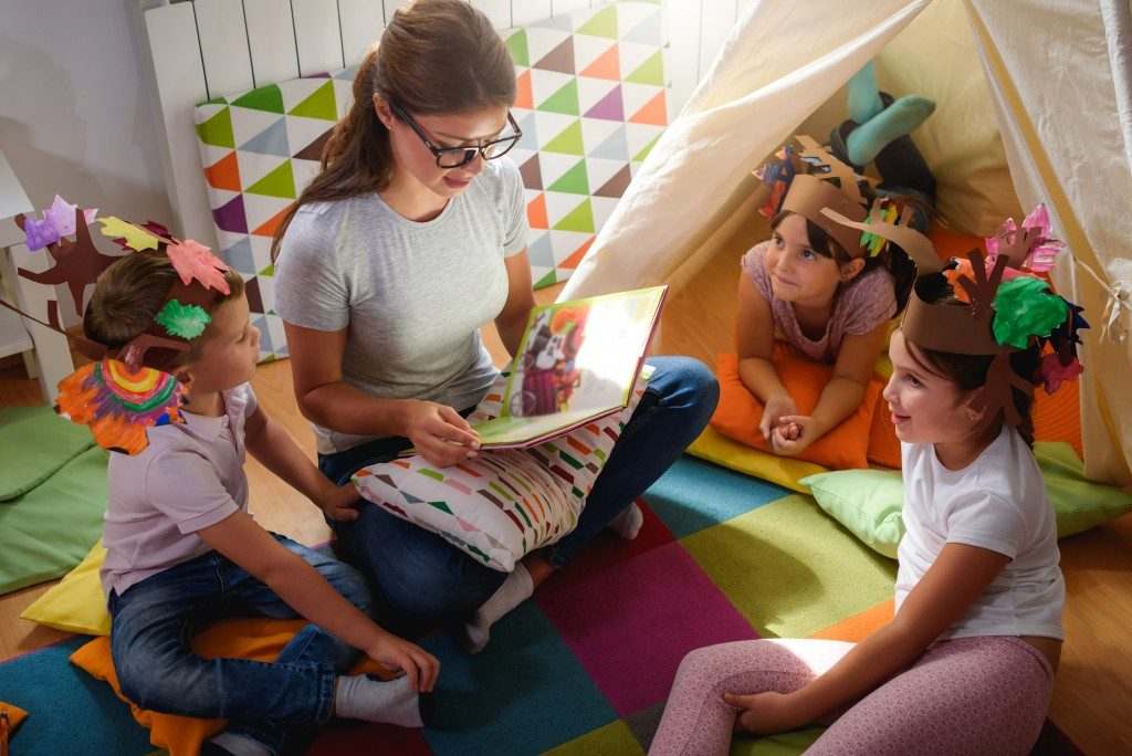 woman reading a story to the kids