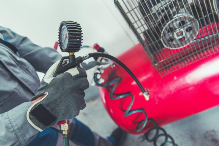 Man adjusting red air compressor