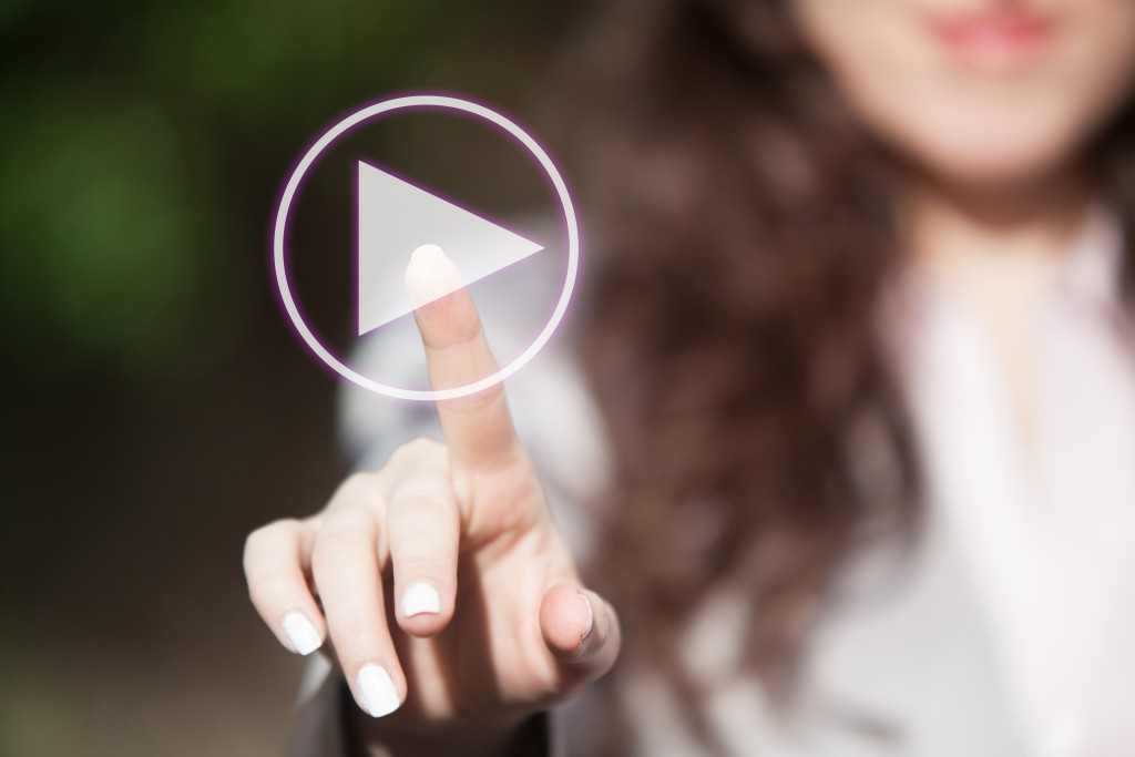 Hand of a woman touching play button on digital display