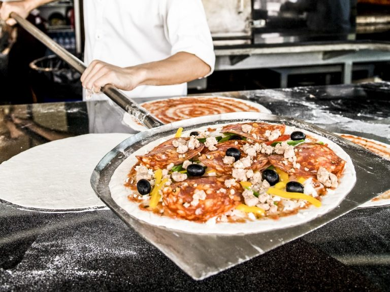 Closeup hand of chef baker in white uniform making pizza