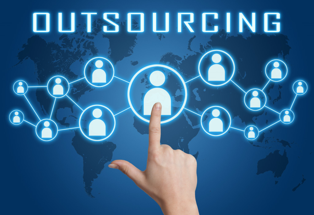 Outsourcing concept with hand pressing social icons on blue world map background