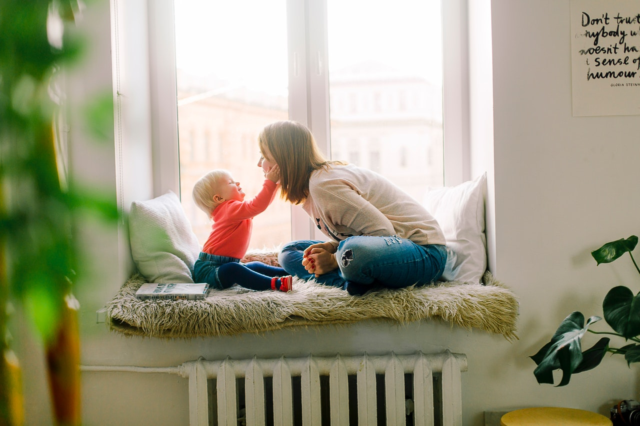 woman playing with child on window sill